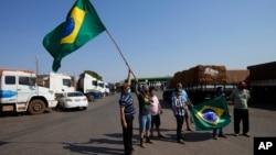 Para sopir truk mengibarkan bendera saat melakukan aksi mogok untuk mendukung pemerintahan Presiden Bolsonaro di Brasilia, Brazil, Kamis (9/9).