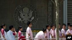 Estudiantes chinos aguardan frente a la embajada de EE.UU. en Beijing para solicitar visas.