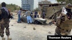 탈레반 병사들이 경계를 서고 있는 가운데 아프가니스탄인들이 로켓 공격에 이용된 차량 사진을 찍고 있다.