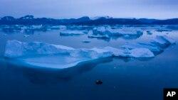ເຮືອນ້ອຍໆ ລຳນຶ່ງກຳລັງພະຍາຍາມແລ່ນຢູ່ຂ້າງແທ່ນນ້ຳແຂງໃຫຍ່ ຢູ່ໃກ້ເມືອງ Kulusuk, ທາງພາກຕາເວັນອອກ ຂອງເກາະ Greenland ໃນວັນທີ 15 ສິງຫາ, 2019