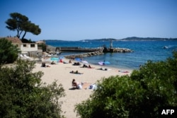FILE - People swim and enjoy a sunny day at 'Les Cigales' beach in Port-Grimaud, with Saint-Tropez in the background, southern France on July 10, 2021.