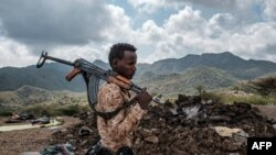FILE - A member of the Afar Special Forces stands in front of the debris of a house in the outskirts of the village of Bisober, Tigray Region, December 9, 2020.