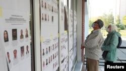 Para pemilih mengenakan asker memeriksa papan informasi di luar tempat pemilihan suara (TPS) dalam pemilu daerah di tengah pandemi virus corona (COVID-19) di Kyiv, Ukraina, 25 Oktober 2020.