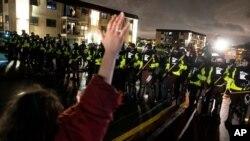 Un manifestante levanta las manos frente a un cerco policial mientras desafían una orden de dispersarse durante una protesta el lunes, 12 de abril, por la noche.