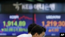 A currency trader watches the computer monitors near the screens showing the Korea Composite Stock Price Index (KOSPI), left, and the foreign exchange rate between U.S. dollar and South Korean won at the foreign exchange dealing room in Seoul, South Korea.