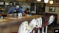 ຕັ່ງທີ່ເອົາຖົງຢາງປລາສຕິກຊຸບໄວ້ ແມ່ນຫ້າມນັ່ງ ເພື່ອຮັກສາໄລຍະຫ່າງກັນ ທີ່ຮ້ານອາຫານ Waffle House ໃນເມືອງຊາແວນນາ ລັດຈໍເຈຍ ວັນທີ 27 ເມສາ 2020.