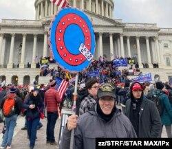 지난 6일 미국 연방의사당에 난입한 시위대 중 한 명이 '큐어넌'을 상징하는 'Q' 자 피켓을 들고 있다.
