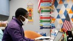 Asisten pengajar Samuel Lavi membantu dengan kelas online di Valencia, Selasa, 2 September 2020, di Phoenix. (Foto: AP)