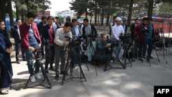 FILE - Afghan journalists gather during a news report at the Shahr-e-Naw Park in Kabul, April 30, 2019.