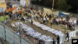 بھگدڑ میں ہلاک ہونے والوں کی میتوں کے گرد امدادی کارکن کھڑے ہیں۔ فائل فوٹو