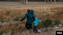 Un migrante guatemalteco y su hijo cruzan la frontera natural de Río Grande entre El Paso, estado de Texas, Estados Unidos, y Ciudad Juárez, estado de Chihuahua, México, en busca de asilo político el 26 de enero de 2021.