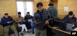 FILE - In this Jan. 30, 2020, photo, Kashmiri journalists browse the internet on their mobile phones inside the media center set up by government authorities in Srinagar, Indian-controlled Kashmir.