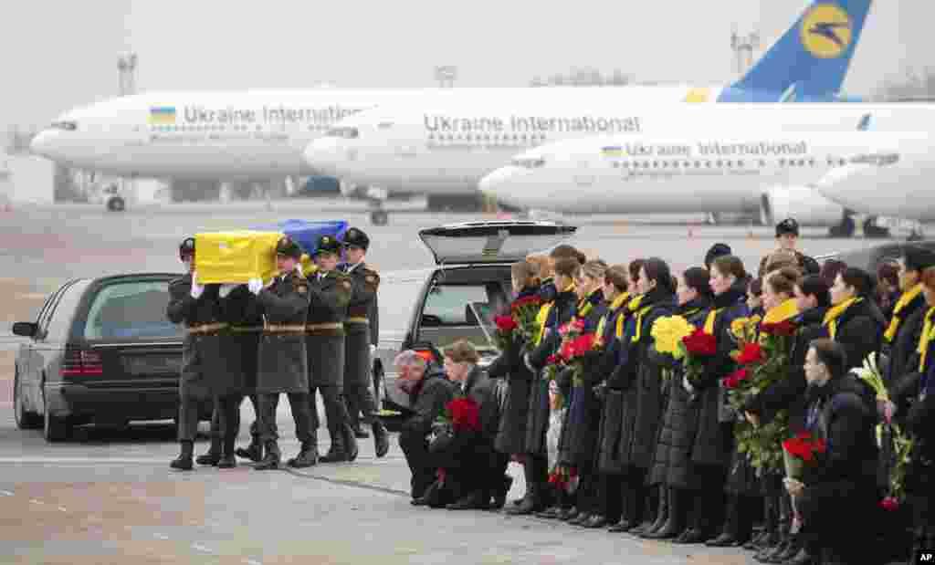 ទាហានកិត្តិយសសែងក្តារមឈូសរបស់ជនរងគ្រោះម្នាក់ក្នុងចំណោមជនរងគ្រោះអ៊ុយក្រែន១១នាក់ ដែលបានជិះយន្តហោះ Boeing 737-800 នៅអាកាសយានដ្ឋានអន្តរជាតិ Borispil ក្នុងប្រទេសអ៊ុយក្រែន។