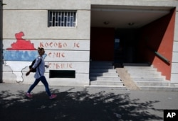 """A woman walks past graffiti on a wall reading: """"Kosovo is the heart of Serbia,"""" in Belgrade, Serbia, Sept. 4, 2020."""