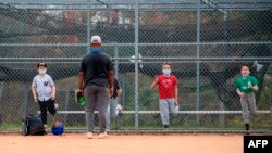 Kids wearing facemasks attend baseball practice at Pan Pacific Park amid the coronavirus pandemic, November 6, 2020, in Los Angeles, California. (Photo by VALERIE MACON / AFP)
