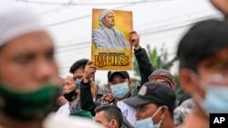 رزاق شہاب کے ایک عقیدت مند نے ایک مظاہرے کے دوران اس کا پوسٹر اٹھایا ہوا ہے۔ جون 24 2021۔