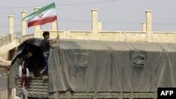 شام کے مشرقی علاقے میں ایک بچہ ایران کے پرچم کے ساتھ ایک فوجی ٹرک پر سوار ہے۔ فائل فوٹو