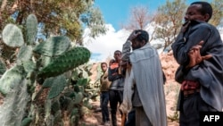 File - People mourn in front of a mass grave the victims of a massacre allegedly perpetrated by neighbouring Eritrean Soldiers in the village of Dengolat, North of Mekele, the capital of Tigray on February 26, 2021.