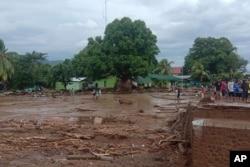 Warga melihat kerusakan di desa yang dilanda banjir bandang di Flores Timur, Minggu, 4 April 2021. (Foto: AP)