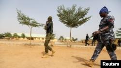 Des policiers marchent à l'école JSS Jangebe, un jour après que plus de 300 écolières ont été enlevées par des bandits, à Zamfara, au Nigeria, le 27 février 2021.