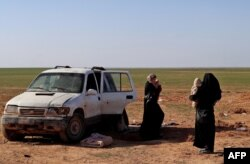 Dua wanita, istri seorang pejuang Negara Islam yang telah diidentifikasi sebagai warga negara Jerman, menunggu untuk diperiksa dan didaftarkan oleh Pasukan Demokrat Suriah, di pedesaan provinsi Deir Ezzor Suriah timur, 31 Januari 2019. (Foto: AFP )