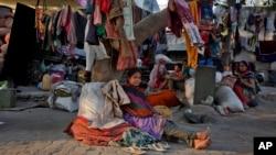 在印度艾哈邁達巴德,工人住在路邊的一棵樹下休息。(2016年1月19日)
