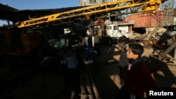 Des Palestiniens inspectent une scène après une attaque aérienne à Gaza, le 5 mai 2016.
