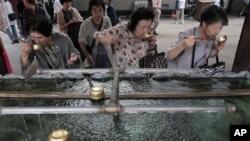 日本老年婦女在東京一處神社用聖水漱口。 (2012年9月29日資料照)