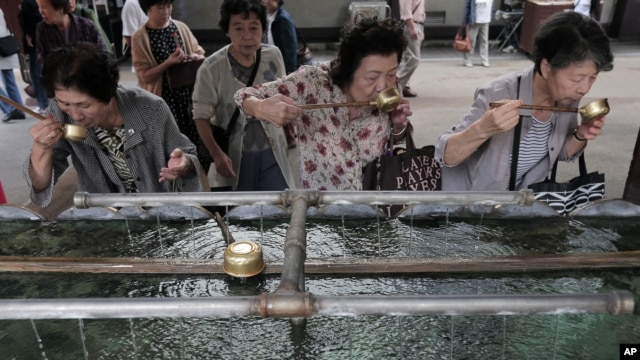 Elderly women rinse their mouths with holy water at a shrine in Tokyo, Japan on Sept. 29, 2012.