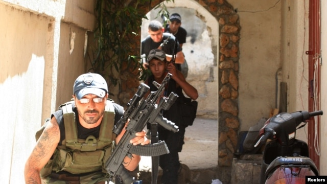 Sunni Muslim gunmen run to take up position in the neighborhood of Bab al-Tebbaneh in Tripoli, northern Lebanon, during sectarian clashes between Sunni Muslims and Alawites, August 24, 2012.