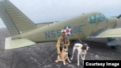 "Pilot Eduard Seitan kneels in front of his plane with two rescue dogs on their way to their new ""forever home."" Seitan is a volunteer for the organization Pilots-n-Paws."