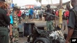 Xavfsizlik xizmati portlagan mashina qoldiqlarini ko'zdan kechirmoqda, Kaduna, Nigeriya, 8-aprel, 2012-yil
