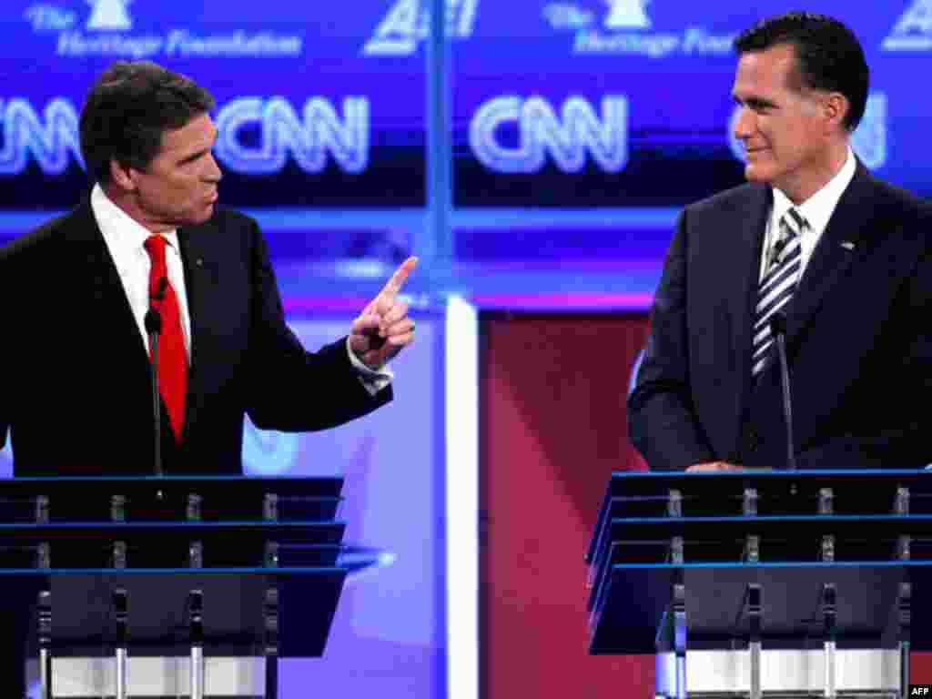 """Ứng cử viên Perry (trái) nói ông muốn trừng phạt Ngân hàng Trung ương Iran để buộc Iran từ bỏ chương trình hạt nhân. """"Đây là một trong những cách mạnh nhất để tạo tác động. Khi ta trừng phạt Ngân hàng Trung ương, cả nền kinh tế sẽ lâm nguy."""" (AP Photo)"""