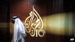 A Qatari employee of Al Jazeera Arabic language TV news channel passes by the logo of Al Jazeera in Doha, Qatar, Wednesday Nov. 1, 2006. The English language offshoot of Qatar based pan-Arab television news channel Al Jazeera said on Tuesday it will sta