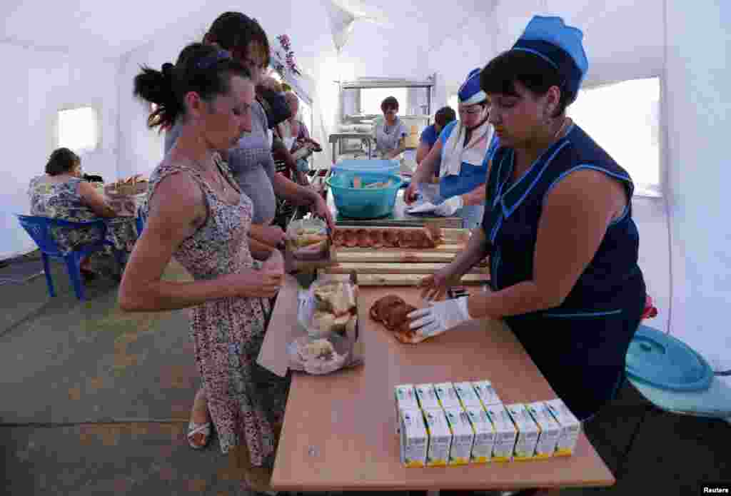 People receive food at a canteen of a refugee camp in Russia's Rostov region, Aug. 18, 2014.