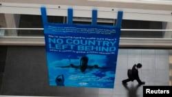 """国际民航组织全球会议期间,一位代表走过该组织的标语""""不落下一个国家""""(2015年2月4日)"""