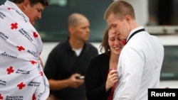 16일 미국 워싱턴의 해군시설에서 총기 난사 사건이 발생해 13명이 사망한 가운데, 한 여성이 건물에서 무사히 나온 남편과 만나 안도하고 있다.