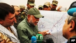 Hadi al-Amiri, leader of the Badr Brigades Shi'ite militia, explains a battle plan to his fighters near the front line on the outskirts of Fallujah in Anbar province, Iraq, June 1, 2015.