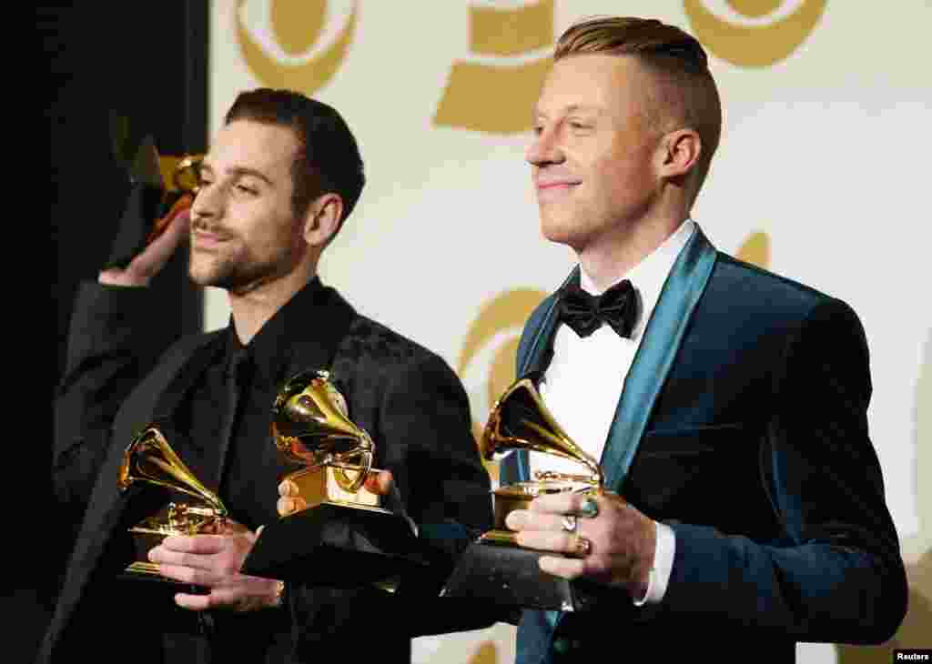 "Macklemore and Ryan Lewis pose backstage with their awards for best new artist, best rap performance for ""Thrift Shop"", best rap song for ""Thrift Shop"", and best rap album for ""The Heist"" at the 56th annual Grammy Awards in Los Angeles, Jan. 26, 2014."