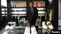 Syrian designer Daniel Essa poses with his prototype luxury sneakers displayed for online sale at a concept store in Lille, France, June 6, 2018.
