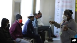 A medical worker addresses some of the first vaccine volunteers, at the Chris Hani Baragwanath hospital in Soweto, Johannesburg Wednesday, June 24, 2020.