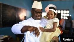 Julius Maada Bio, calon presiden Partai Rakyat Sierra Leone (SLPP), menggendong putrinya saat memasukkan surat suaranya ke kotak suara saat berlangsungnya pemilihan umum Sierra Leone di Freetown, Sierra Leone, 7 Maret 2018.