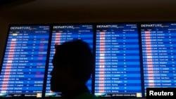 Seorang pria melintas di depan papan berisi jadwal penerbangan di Bandar Udara Internasional Kuala Lumpur 2 (KLIA2) di Sepang (30/4). (Reuters/Samsul Said)
