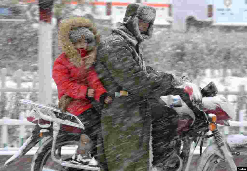 Seorang pengendara sepeda motor membawa seorang anak saat turun hujan salju di Balikun, Xinjiang, Uighur, China.