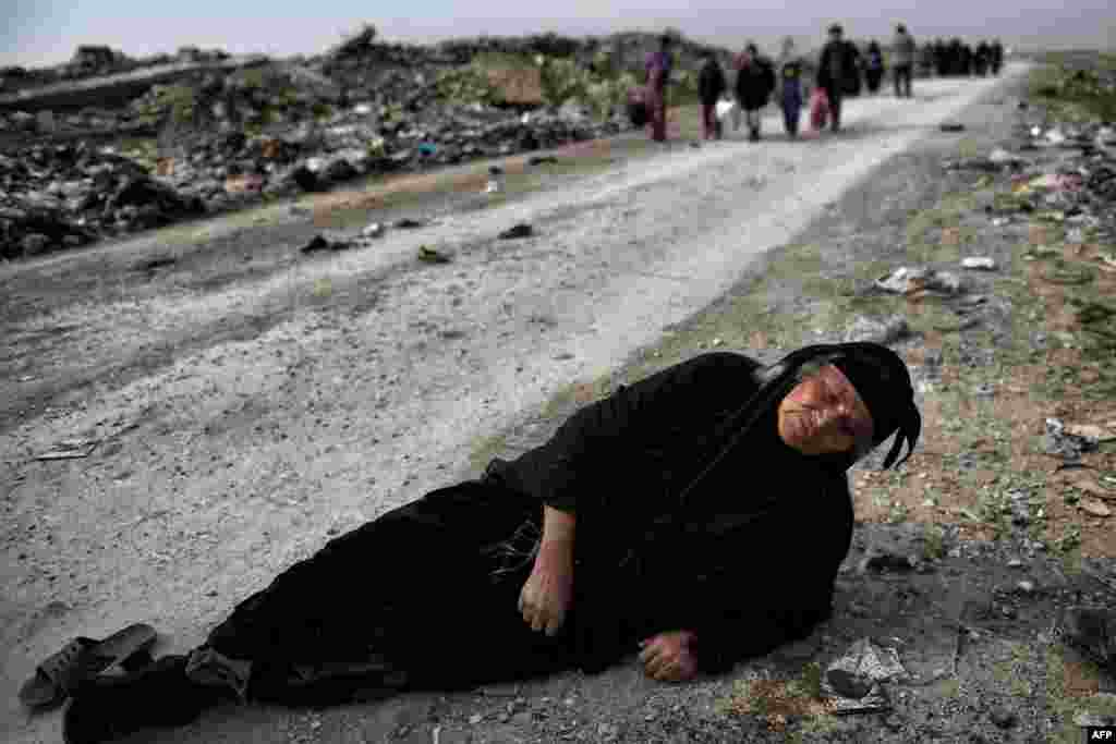 A woman lies on the ground while civilians flee Mosul as Iraqi forces advance inside the city, during fighting against Islamic State militants.