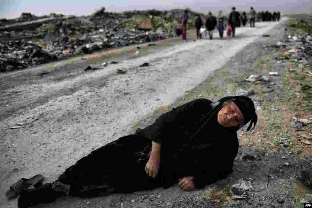 ស្រ្តីម្នាក់ទម្រេតខ្លួនលើដីខណដែលប្រជាជនស៊ីវិល រត់គេចពីទីក្រុង Mosul ខណដែលកងកម្លាំងពិសេសរបស់អ៊ីរ៉ាក់ កំពុងប្រយុទ្ធនឹងយុទ្ធជនរដ្ឋឥស្លាមខាងក្នុងទីក្រុង។