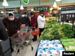 FILE - People wearing masks shop at a supermarket on the second day of the Chinese Lunar New Year, following the outbreak of a new coronavirus, in Wuhan, Hubei province, China, Jan. 26, 2020.