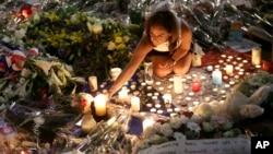 Một người phụ nữ thắp nến tưởng niệm những nạn nhân vụ khủng bố ở Nice, miền Nam nước Pháp, 18/7/2016.