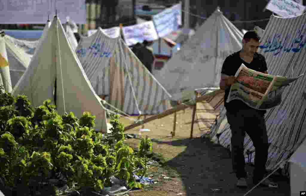 A protester reads the Wafd, a local newspaper next to tents occupied by protesters in Tahrir Square, in Cairo, Egypt, November 28, 2012.