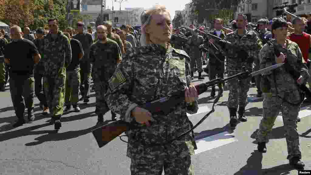Armed pro-Russian separatists escort a column of Ukrainian prisoners of war, left, as they walk across central Donetsk, Ukraine, Aug. 24, 2014.